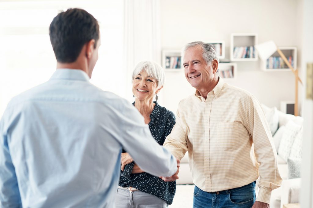 Elderly couple shaking hands with businessman